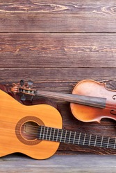 Guitar, violin and copy space. Acoustic guitar and violin on textured wooden background. Instruments for musician.