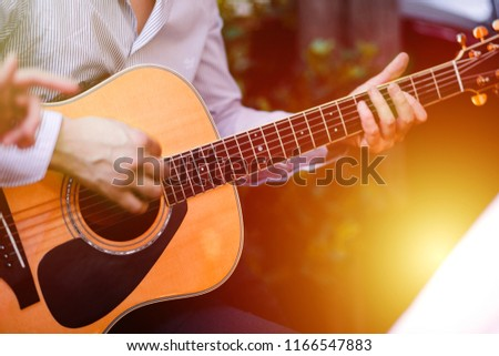 Guitar with a man's male hands playing the guitar on wooden wall background, electric or acoustic guitar with nature light. Concept of guys boys band performing on events  #1166547883