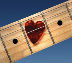 Guitar with heart-shaped pick. Closeup of fretboard.