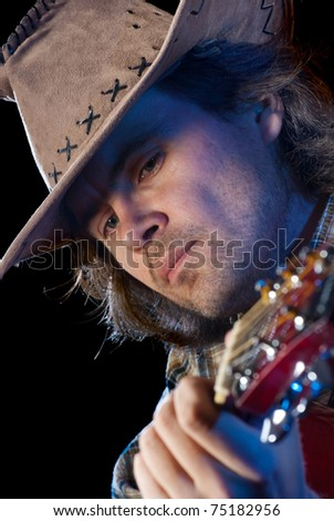 Guitarist. Closeup shoot of man wearing cowboy hat playing on a acoustic guitar. Isolated on black background.