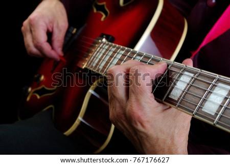 Guitarist hands and guitar close up