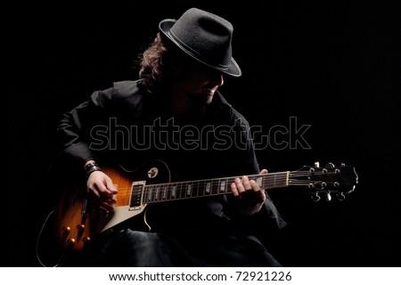 Guitarist in black hat playing guitar