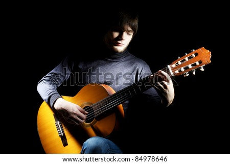 Guitarist musical instrument guitar acoustic. Musician man concert playing on black