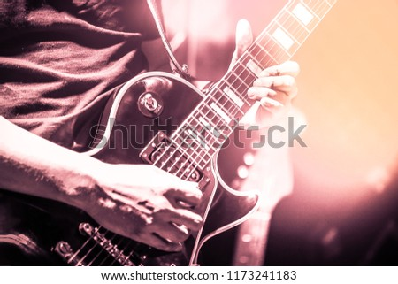 Guitarist on stage for background, soft and blur concept. Close up hand playing guitar. young musician playing guitar, live music background.Band performs on stage, rock music concert. #1173241183