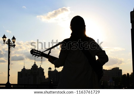 guitarist on the waterfront, guitarist on the background of the sun