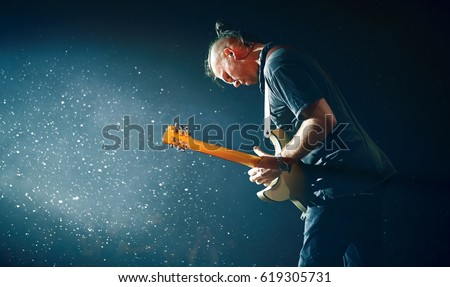Guitarist performing on stage. Concert. Stage light #619305731