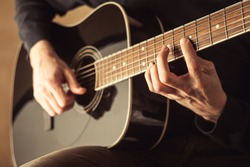guitarist playing acoustic guitar close-up shot