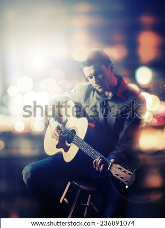 Guitarist playing acoustic guitar. Unplugged performance in the dark.
