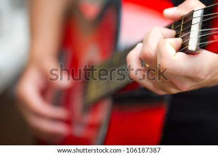 Guitarist playing jazz on red acoustic guitar