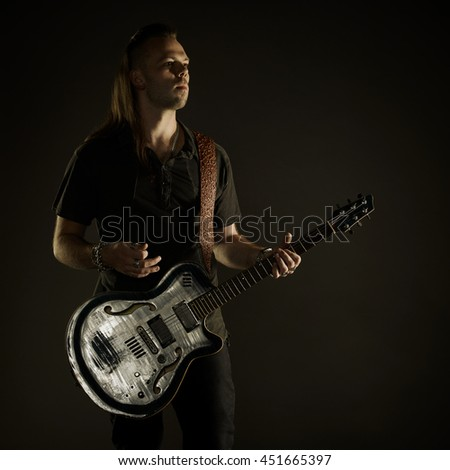 Guitarist playing rock music. On dark background. Beautiful guitar. Foto stock ©