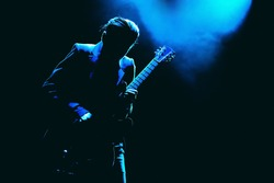 Guitarist silhouette in a dark on a stage in blue lights playing solo
