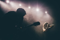 Guitarist silhouette on a stage in a backlights in the smoke playing solo with the female singer at background
