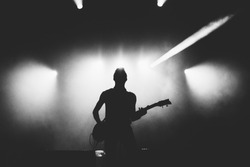 Guitarist silhouette on a stage in a bright stage lights. Black and white