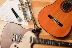 Guitars, trumpet, microphone and note sheets on wooden background, flat lay. Musical instruments
