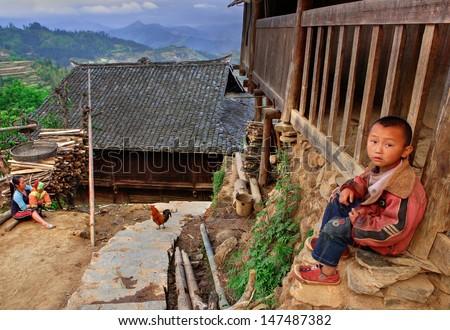 GUIZHOU PROVINCE; CHINA - APRIL 10: 7 years old boy near a wooden house in the village of ethnic minority Miao, April 10, 2010. Basha Miao Village, Congjiang County, Southeast Guizhou, Southwest China
