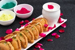 Gujiya Or Gujia Mithai Made In Desi Ghee Pista Badam Served With Cold Thandai Bhang On Occasion Of Happy Holi. Colorful Gulal Abeer Or Abir And Floral Decoration On Black Background With Copy Space