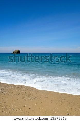 Gull rock island, the beach, blue summer sky and sea in Portreath, Cornwall UK.