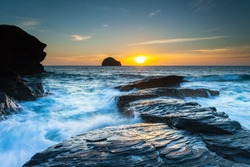 Gull Rock Sunset.  The sun sets beyond Gull Rock as the tide crashes in. At Trebarwith Strand, Cornwall, UK.