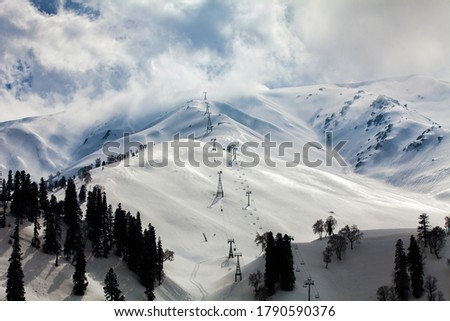 Gulmarg snow in the middle of Himalaya mountain at Kashmir. Snow against Sun light at Gulmarg village. Landscape of beautiful nature of Himalaya mountain at blue sky.