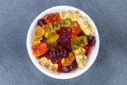 Gummy bears sweets gummybears from above bowl on a slate