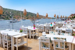 Gumusluk, a seaside village and fishing port in Bodrum, Turkey. Tables and Chairs are in the Sea.