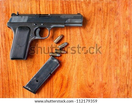 Gun and bullets on wood  table - stock photo