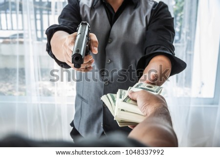 Gun and money in a hands. Bank robbery, Man carrying a gun to rob the money. To threaten with the gun man