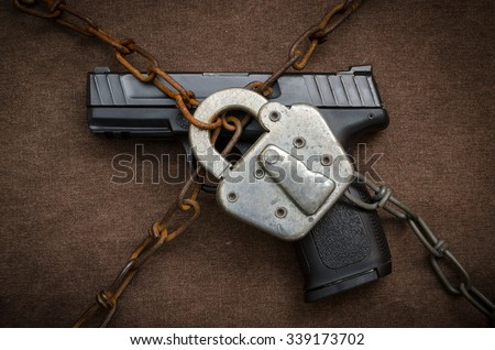 Gun Control Concept - Pistol behind Lock and Chain
