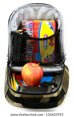 Gun in the lunch box with an apple and other school supplies studio concept shot.
