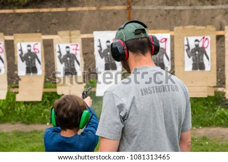 Gun instructor teaching young kid how to shoot from firearm at shooting range