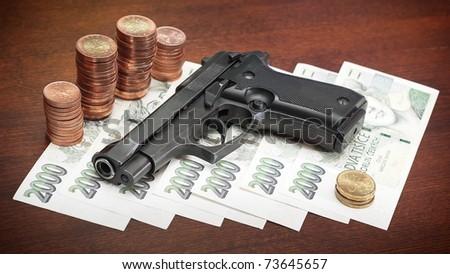 Gun on money symbolising money-related criminality.