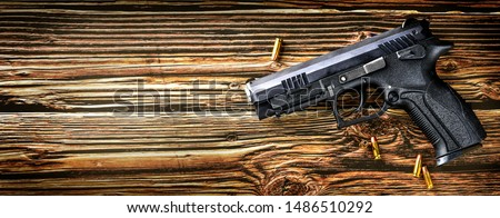 Gun with ammunition on dark stone background. Guns ammo or rounds military picture top view.