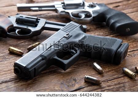 Gun with ammunition on wooden background.