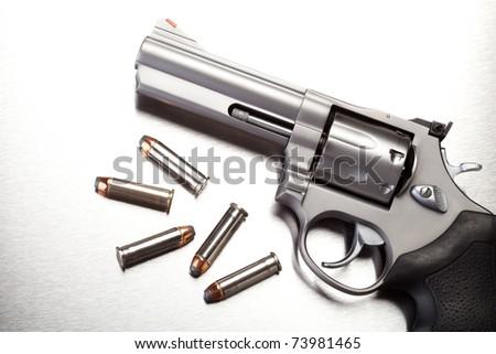 Stock Photo gun with bullets on steel surface - modern revolver handgun