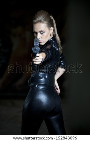 gun woman in leather suit over black