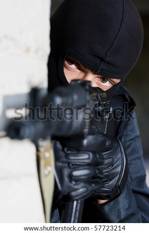 Gunman aiming his target with an automatic russian AK-47 rifle