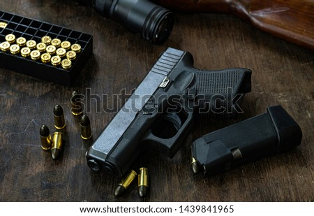 Guns and ammunition placed in a wooden table,Short guns and ammunition placed on a black background table,Guns and ammunition are ready to use.,Noisy weapon