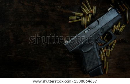 Guns and ammunition placed in a wooden table,Short guns and ammunition placed on a black background table,Guns and ammunition are ready to use. Noisy weapon
