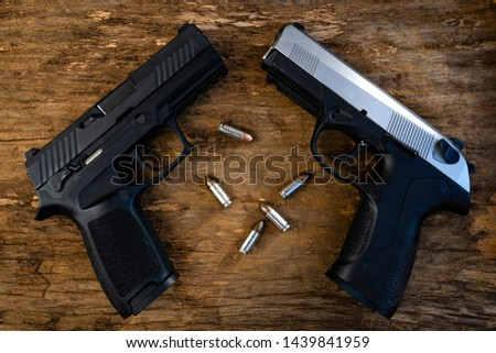 Guns and ammunition placed in a wooden table,Short guns and ammunition placed on a brown wood table,Guns and ammunition are ready to use.,Noisy weapon,Murder weapon #1439841959