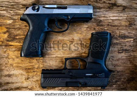 Guns and ammunition placed in a wooden table,Short guns and ammunition placed on a brown wood table,Guns and ammunition are ready to use.,Noisy weapon,Murder weapon #1439841977