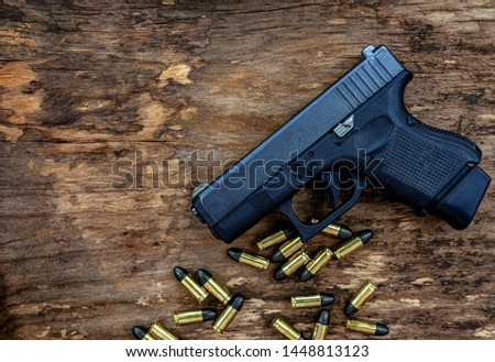Guns and ammunition placed in a wooden table,Short guns and ammunition placed on a brown wood table,Guns and ammunition are ready to use.,Noisy weapon,Murder weapon #1448813123