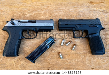 Guns and ammunition placed in a wooden table,Short guns and ammunition placed on a brown wood table,Guns and ammunition are ready to use.,Noisy weapon,Murder weapon #1448813126