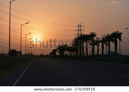 Gurgaon, India  urban road and High-voltage tower power wires with sunset and sky background