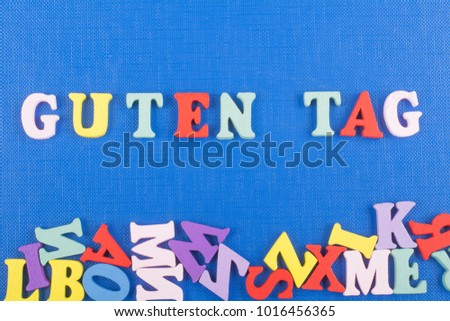 GUTEN TAG word on blue background composed from colorful abc alphabet block wooden letters, copy space for ad text. Learning english concept
