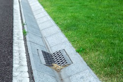 gutter of a stormwater drainage system in perspective on the side of an road with markings and lawn.