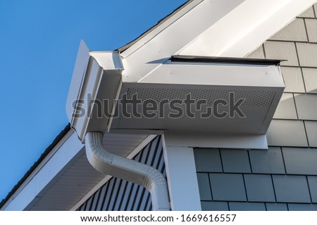 Gutter system that collects water shedding off the roof, with slip connector, end cap, elbow tube, gutter hanger, gutter drop connecting  outlet to the downspout, soffit, fascia, gray shingle siding Stock photo ©