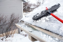 Gutters with ice dam and broom for raking snow off of a roof
