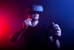 guy a gamer in modern wireless glasses of virtual reality plays a shooter, a man is focused on a 3D game in a dark room