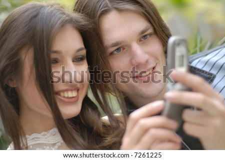 guy and  girl look mobile phone