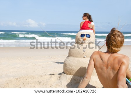 Guy and girl on christmas beach having with perfectly build snowman made out of sand wearing sunglasses.